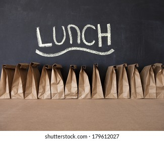 A row of brown bags against a blackboard with the word 'lunch'.