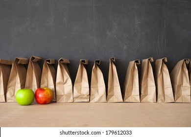 A row of brown bags against a blackboard.