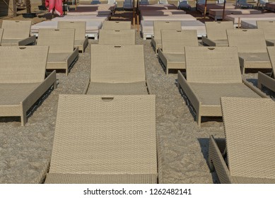 row of brown wicker loungers on the beach in the sand