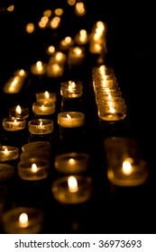 Row of burning candles in the dark