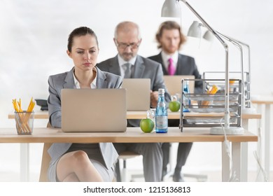 Row of business colleagues using laptops at desks in office.creative conceptual photo showing that people become trapped in their jobs and careers that takes up all their time