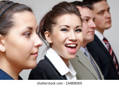 Row of business people with focus on cheerful businesswoman
