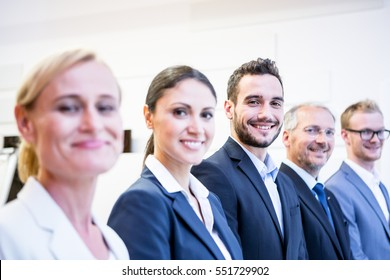 Row of business people, focus on man in center, Caucasian European team in office environment
