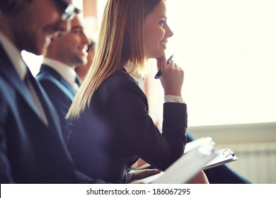 Row of business people making notes at seminar, focus on attentive young female