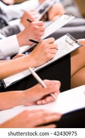 Row of business people making notes at seminar