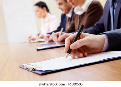 Row of business people making notes with focus on hand holding pen