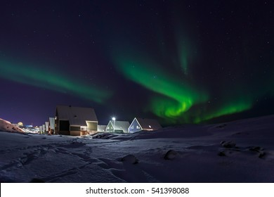 Row of cabins and green Northern lights in a suburb of Nuuk