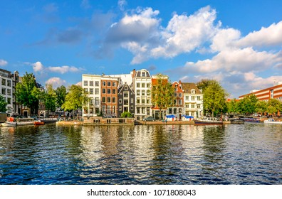A row of canal homes stacked together tightly on a canal in the museum district of Amsterdam, The Netherlands