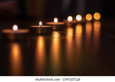 A row of candles on a dark background.