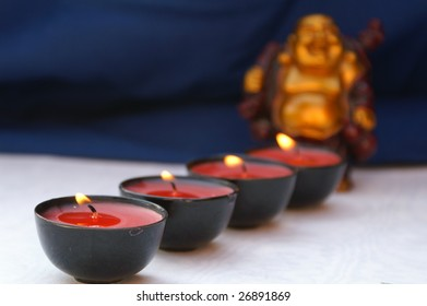 a row of candles with small buddha