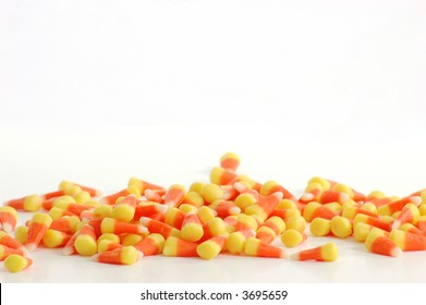 Row of candy corn against a white backdrop.
