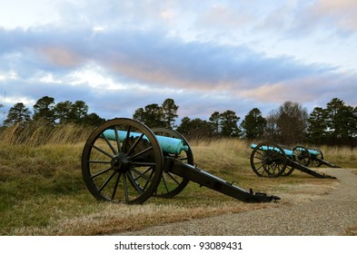 row of cannons aimed over earthwork