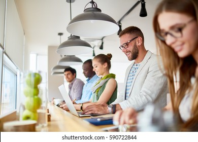 Row of casual business people  smiling while working with laptops at standing workplace in modern light office