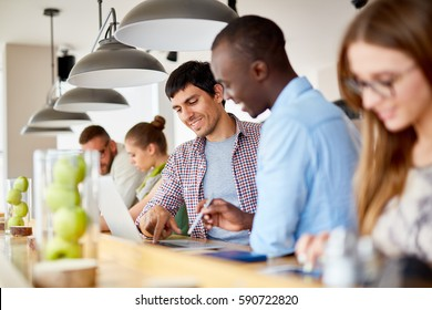 Row of casual business people  working with laptops at standing workplace and discussing projects in modern light office