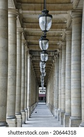Row of ceiling lamps flanked by columns lined in parallel