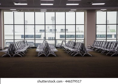 Row of chairs at airport lounge, airport lobby with no one and have windows at the back of image. Seats for tourist are waiting for boarding flight at the gate.