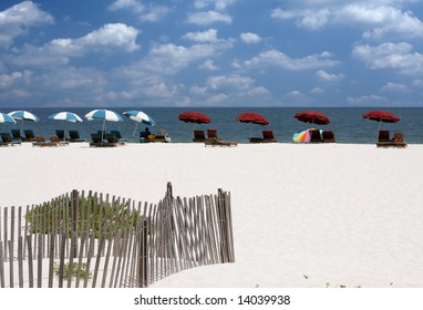 A row of chairs and umbrellas on a sandy white beach in Gulf Shores, AL.
