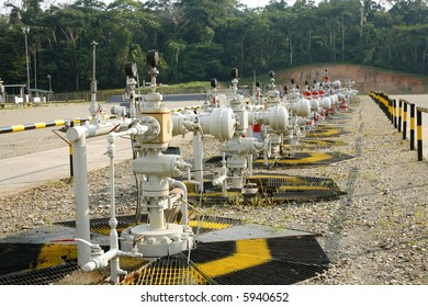 row of christmas tree valves on an oil well in the Amazon