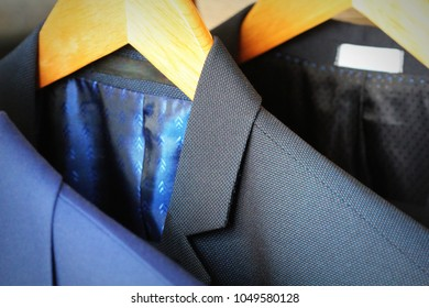 Row of classic men's suits hanging for sale