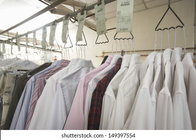 Row of clean clothes hanging on hanger in laundry