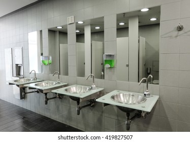 Row of clean and new sinks and taps in a public toilet
