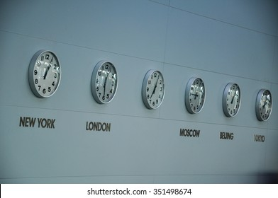 A row of clocks in an airport, with a variety of times shown for major cities.