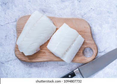 Row cod fillets on wooden board - top view