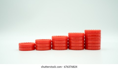 Row of coin rising stacks isolated on white background for money saving plan or financial growth concept. Stacks of red plastic coin shape from table game. Symbolic image