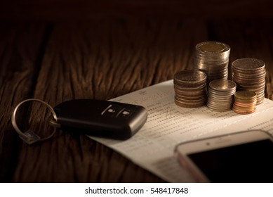 Row of coins on account book, mobile and car key remote, car finance concept.
