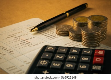 row of coins,calculator on the account book and pen on the wooden table and black background in finance and banking concept