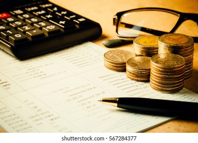 Row of coins,pen,glasses and calculator on the wooden table in finance and banking concept