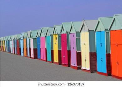 row of colored beach huts with blue sky background