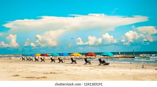 A row of colorful beach umbrellas and beach loungers on Galveston Island Texas.
