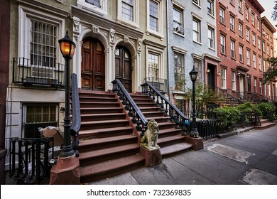 a row of colorful brownstone buildings with a warm gas lamp in a famous neighborhood in Manhattan, New York City.