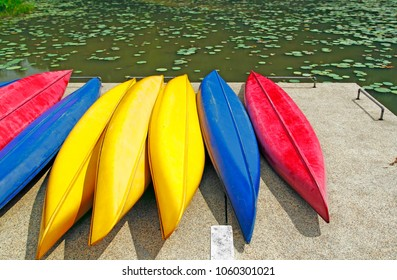 A row of colorful canoe parked on lakeside jetty.