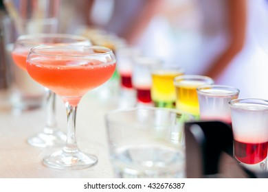 A row of colorful cocktail drinks and liquor shots in a cocktail bar