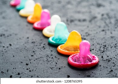 Row of colorful condoms over black table. Safe sex concept