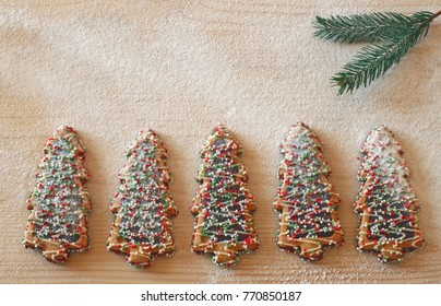row of colorful decorated Christmas tree cookies covered with sugar and a pine branch on bright wood