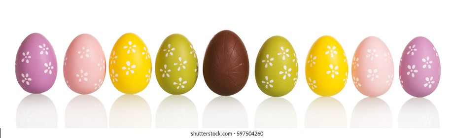 Row of colorful Easter eggs in the center of chocolate egg, isolated on white background.