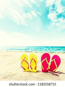 Row of colorful flip flops on beach