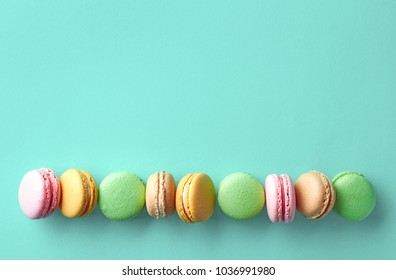 Row of colorful french macarons on blue background. Top view. Pastel colors