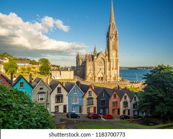 Row of colorful houses with cathedral backround in Cobh Ireland