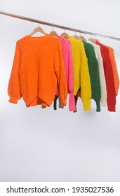 Row of colorful Knitted, sweaters hang on hangers