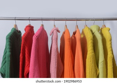 row of colorful Knitted, turtleneck sweaters hang on hangers-gray background
