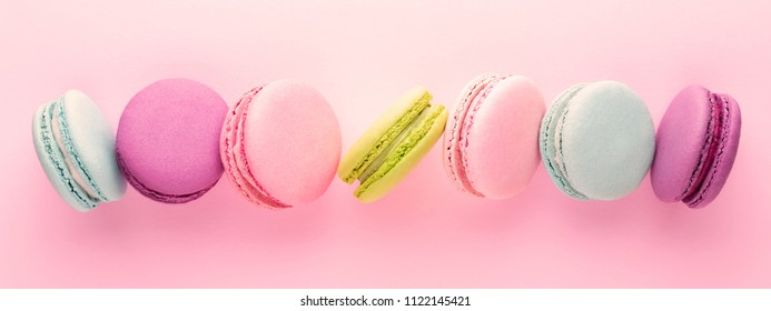 The row of colorful macarons on pink background. Top view. Banner.