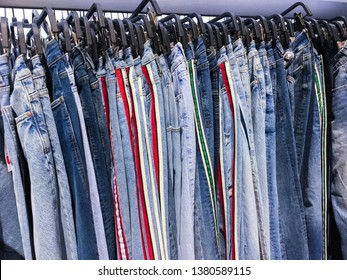 Row of Colorful man and woman's blue jeans and striped pants on hangers in a retail shop