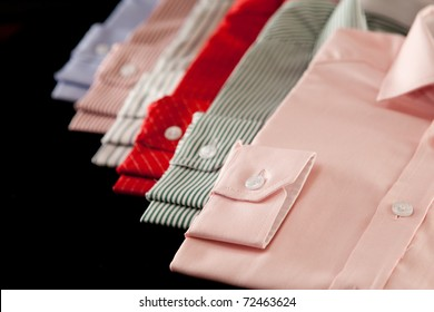 Row of colorful mens' shirts showing the cuffs