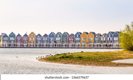 Row of colorful modern houses along water in a family friendly suburban neighborhood in Houten in the Netherlands.