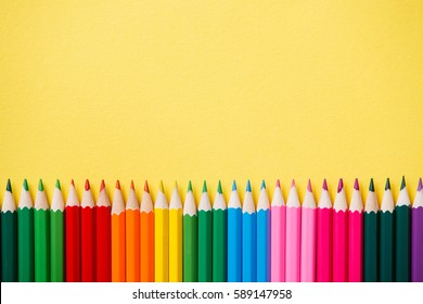Row of colorful pencils on yellow background