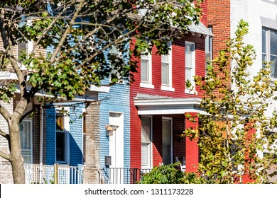 Row of colorful red and blue painted brick residential townhouses homes houses architecture exterior entrance in Washington DC Capitol Hill neighborhood district